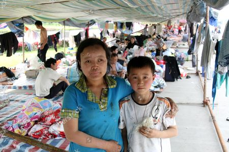 Refugee boy Zhou Kai and his mother Mao Xin Li, survivors of the chinese earthquake at a temporary roadside camp in Shifang