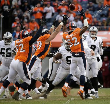 Oakland Raiders quarterback Connor Cook (8) passes to wide receiver Michael Crabtree (not shown) under pressure from Denver Broncos' Sylvester Williams (92), Adam Gotsis (99) and Corey Nelson (52) in the second half of an NFL football game, in Denver