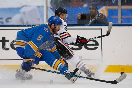 Joel Edmundson, Ryan Hartman St. Louis Blues' Joel Edmundson, left, and Chicago Blackhawks' Ryan Hartman race for the puck along the boards during the first period of the NHL Winter Classic hockey game at Busch Stadium, in St. Louis