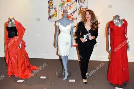 Jerry Hall with - (L) -An Edina Ronay black mock-croc bustier and shot flame-red taffeta evening skirt and stole, 2005 - (M)  The Anthony Price white lace wedding dress she wore to marry Jagger in 1990 - (R) A Bruce Oldfield scarlet swathed chiffon evening gown 1990's