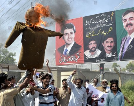 Supporters of Ruling Pakistan People Party Burn an Effigy of Supreme Court's Chief Justice Iftikhar Muhammad Chaudhry As They Shout Slogans After the Supreme Court Convicted the Prime Minister Yusuf Raza Gilani (pictured Right) of Contempt in Multan Pakistan 26 April 2012 Pakistan's Supreme Court on 26 April Convicted Prime Minister Yousuf Raza Gilani of Contempt of Court Meaning He Cannot Hold Public Office But Imposed Only a Symbolic Punishment Ordered Him to Stay in the Courtroom As Punishment Until the Judges Left Gilani was Found Guilty For Failing to Write to the Swiss Authorities to Ask Them to Re-open Graft Cases Against President Asif Ali Zardari who Heads the Pakistan People's Party to Which Gilani Also Belongs Despite a Court Order to Do So Pakistan Multan