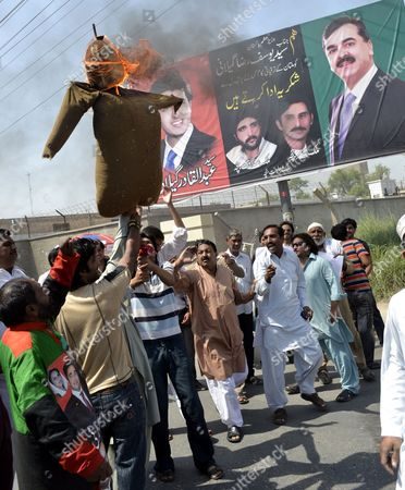 Supporters of Ruling Pakistan People Party Burn an Effigy of Supreme Court's Chief Justice Iftikhar Muhammad Chaudhry As They Shout Slogans After the Supreme Court Convicted the Prime Minister Yusuf Raza Gilani (pictured at Right) of Contempt in Multan Pakistan 26 April 2012 Pakistan's Supreme Court on 26 April Convicted Prime Minister Yousuf Raza Gilani of Contempt of Court Meaning He Cannot Hold Public Office But Imposed Only a Symbolic Punishment Ordered Him to Stay in the Courtroom As Punishment Until the Judges Left Gilani was Found Guilty For Failing to Write to the Swiss Authorities to Ask Them to Re-open Graft Cases Against President Asif Ali Zardari who Heads the Pakistan People's Party to Which Gilani Also Belongs Despite a Court Order to Do So Pakistan Multan