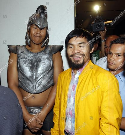 Philippine Boxing Icon Manny Pacquiao Smiles As He Walks Past a Hotel Staff Dressed As Ancient Greek Warrior Upon His Arrival at a Hotel in Pasay South of Manila Philippines 16 June 2012 Pacquiao Lost His World Welterweight Title to Undefeated Us Challenger Timothy Bradley on 10 June Bradley Won by a Split Decision Improving His Record to 29 Wins Zero Defeat and One No-contest It was Pacquiao's First Defeat in Seven Years Since He Lost to Mexican Erik Morales in 2005 Philippines Manila