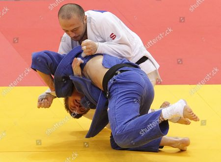 Stock Picture of Alim Gadanov of Russia (white) in Action Against Tomasz Kowalski of Poland (blue) During Their Men's - 66 Kg Final Match at the European Judo Championships at the Traktor Arena in Chelyabinsk Russia 26 April 2012 Russian Federation Chelyabinsk