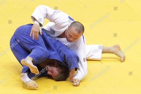 Stock Photo of Alim Gadanov of Russia (white) in Action Against Tomasz Kowalski of Poland (blue) During Their Men's - 66 Kg Final Match at the European Judo Championships at the Traktor Arena in Chelyabinsk Russia 26 April 2012 Russian Federation Chelyabinsk