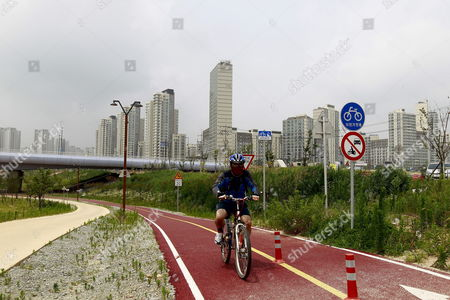 A South Korean Rides a Bicycle Near the Residential Area in the Sejong Special Self-governing City Construction Site in Sejong City 120km South of Seoul South Korea 04 July 2012 South Korea on 02 July 2012 Officially Launched a Planned Government City Which is to House Several Key Ministries Sejong City is to Be Home to 36 Departments by 2014 Including the Office of the Prime Minister and Several Ministries the President Parliament and Key Portfolios Including Foreign Defence and Unification Ministries Are to Remain in Seoul the 22 5-billion-won (19-billion-dollar) 'World Class City' is Still Under Construction But Will Be Home to Half a Million People by 2030 Premier Kim Hwang Sik Sid at the Ceremony Korea, Republic of Sejong