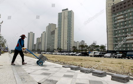 A South Korean Worker Laying Tiles of a Pavement in the Residential Area of the Sejong Special Self-governing City Construction Site in Sejong City 120km South of Seoul South Korea 04 July 2012 South Korea on 02 July 2012 Officially Launched a Planned Government City Which is to House Several Key Ministries Sejong City is to Be Home to 36 Departments by 2014 Including the Office of the Prime Minister and Several Ministries the President Parliament and Key Portfolios Including Foreign Defence and Unification Ministries Are to Remain in Seoul the 22 5-billion-won (19-billion-dollar) 'World Class City' is Still Under Construction But Will Be Home to Half a Million People by 2030 Premier Kim Hwang Sik Sid at the Ceremony Korea, Republic of Sejong