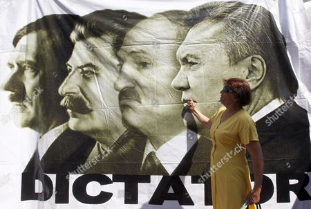 A Ukrainian Woman Makes a Rude Gesture in Front of Poster Showing Dictators (l-r) Adolf Hitler Josef Stalin Aleksandr Lukashenko and Ukrainian President Viktor Yanukovych During a Demonstration Marking the 300th Day of Imprisonment For Ukrainian Ex-premier Yulia Tymoshenko in a Tent Camp Set Up by Her Suppoprters Near of the Pechersk Court in Kiev Ukraine 30 May 2012 a Ukrainian Court Ordered the Detention of Former Prime Minister Yulia Tymoshenko on 05 August 2011 Tymoshenko was Sentenced to Seven Years in Prison on 11 October 2011 For Abuse of Power She Had Exceeded Her Authority As Prime Minister to Approve an Unfavourable Natural Gas Import Deal with Russia in 2009 and Caused Some 187 Million Dollars in Losses to Taxpayers the Court Had Ruled Ukraine Kiev