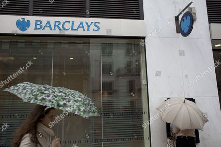 A Woman Walks Past a Barclay's Branch As a Person Uses a Cash Machine in London Britain on 02 July 2012 the Chairman of Barclays Bank Marcus Agius Said 02 July 2012 He Would Step Down After the British Bank was Fined For Fixing Inter-bank Interest Rates Agius who Has Served As Chairman Since 2007 Will Remain in His Job Until 'An Orderly Succession is Assured ' the Departure Comes a Week After Barclays was Hit with a 290-million-pound (451 6 Million Dollar) Fine by Us and British Regulators Because of Manipulation of a Key Interbank Lending Rate United Kingdom London