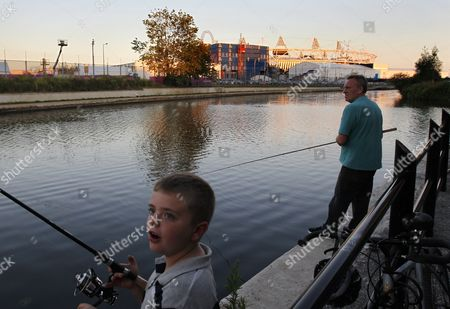 Picture Made Available 24 July 2012 of British Local Resident Andrew Wright (r) and His Grandson Teddy Fishing in the Canal That Goes Around and Through the Large Olympic Park Near where They Live with the Main Olympic Stadium Seen in Background As Athletes Start Training Ahead of the Start of the London Olympics in London Britain 23 July 2012 Wright Has Been Fishing the Canal For 50 Years with a Local License and Has Resisted Being Moved on by Security That Are Surrounding the Olympic Park to Protect Against Any Attack United Kingdom London