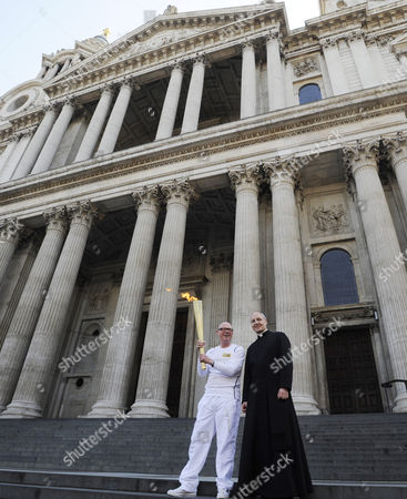Torchbearer John Elbrow (l) Carries the Olympic Flame on the Torch Relay Leg in St Pauls Cathedral Next to the Dean of St Pauls David Ison (r) in London Britain 26 July 2012 on the Penultimate Day of the Torch Relay the Olympic Flame Will Travel Through the Heart of London From Camden to Westminster United Kingdom London