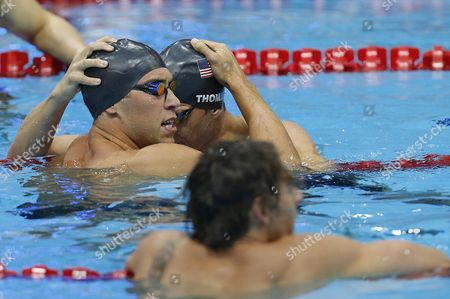 Stock Photo of Winner Matthew Grevers (l) of the United States of America (usa) and His Teammate Second Placed Nick Thoman (c) Celebrate After Competing in the Men's 100m Backstroke Final While 4th Placed Camille Lacourt (front) of France is Disappointed During the Swimming Competition Held at the Aquatics Center During the London 2012 Olympic Games in London England 30 July 2012 United Kingdom London