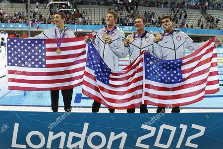 (l-r) Michael Phelps of the Usa and His Teammates Conor Dwyer Ryan Lochte and Ricky Berens Pose with Their Gold Medals and an Us Flags After the Award Ceremony For the Men's 4x200m Freestyle Relay Final During the Swimming Competition Held at the Aquatics Center During the London 2012 Olympic Games in London England 31 July 2012 This is Phelps 19th Olympic Medal Which Makes Him the Most Decorated Olympian of All Time United Kingdom London
