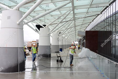 Stock Image of A Construction Worker Power Washes the Sidewalk of the New Maynard H Jackson Jr International Terminal at Hartsfield-jackson Atlanta International Airport in Atlanta Georgia Usa on 22 March 2012 the 1 2 Million-square-foot Terminal is Scheduled to Open 16 May 2012 the Facility Connects with the Existing International Concourse Creating a 40-gate Complex the International Terminal Will Eliminate the Need For Atlanta-bound Passengers to Recheck Their Baggage United States Atlanta