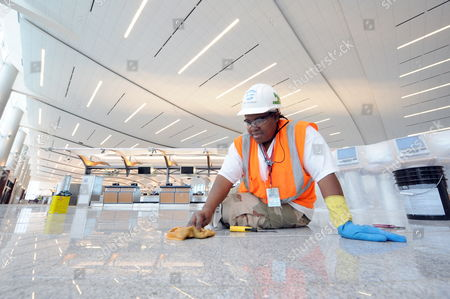 Cora Amerson Does Some Final Work on the Granite Floor in the Ticketing Area at the New Maynard H Jackson Jr International Terminal of Hartsfield-jackson Atlanta International Airport in Atlanta Georgia Usa on 22 March 2012 the 1 2 Million-square-foot Terminal is Scheduled to Open 16 May 2012 the Facility Connects with the Existing International Concourse Creating a 40-gate Complex the International Terminal Will Eliminate the Need For Atlanta-bound Passengers to Recheck Their Baggage United States Atlanta