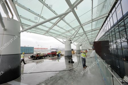 A Construction Worker Power Washes the Sidewalk of the New Maynard H Jackson Jr International Terminal at Hartsfield-jackson Atlanta International Airport in Atlanta Georgia Usa on 22 March 2012 the 1 2 Million-square-foot Terminal is Scheduled to Open 16 May 2012 the Facility Connects with the Existing International Concourse Creating a 40-gate Complex the International Terminal Will Eliminate the Need For Atlanta-bound Passengers to Recheck Their Baggage United States Atlanta