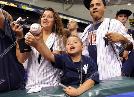 Stock Photo of D J Hernandez 5 is Joined by His Father Derek Hernandez and Mother Alex Ott As He Yells For New York Yankees Shortstop Derek Jeter to Come Sign His Ball Before the Start of a Major League Baseball Game Between the Yankees and the Tampa Bay Rays in St Petersburg Florida Usa 07 April 2012 United States St. Petersburg