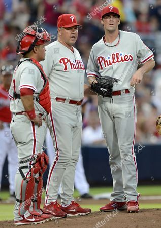 Philadelphia Phillies Starting Pitcher Starting Pitcher Cole Hamels (r) and Catcher Carlos Ruiz (l) Listen to Philadelphia Phillies Pitching Coach Rich Dubee As They Face the Atlanta Braves in the Second Inning of Their Mlb Baseball Game in Atlanta Georgia Usa 27 July 2012 United States Atlanta