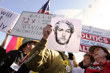 An Opponent (c) of the Health Care Reform Holds a Sign Depicting Conservative Blogger Andrew Breitbart Outside the Supreme Court As the Justices Hear Oral Arguments on Cases Related to Health Care Reform Law in Washington Dc Usa 27 March 2012 Passing a Major Reform of the Us Health Insurance System was President Barack Obama's Signature Legislative Achievement the Culmination of Decades of Efforts by Centre-left Democrats to Change the System United States Washington