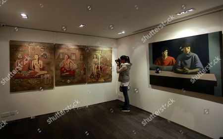 A Report Takes Pictures of a Painting by Chinese Painter Zhang Xiaogang Entitled 'Forever Lasting Love Series (triptych)' (l) and a Painting by Chinese Painter Geng Jianyi Entitled 'Two People Under a Light' During a Press Preview in Hong Kong China 17 February 2011 the Paintings Will Be Auctioned As Part of Sotheby's Hong Kong Evening Sale of the Ullens Collection Which Will Be Held on 03 April This Year China Hong Kong