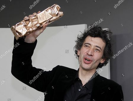 French Actor Eric Elmosnino Holds His Best Actor Award For His Role in 'Gainsbourg (vie Heroique)' As He Poses For Photographs in the Press Room During the 36th Cesar Awards Ceremony Held at the Chatelet Theatre in Paris France 25 February 2011 the 'Academie Des Arts Et Techniques Du Cinema' of France Honours Excellence in 21 Categories France Paris
