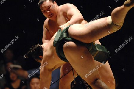 Kotooshu (Green) and Hakuho (Brown) wrestle during the quarter finals of their match