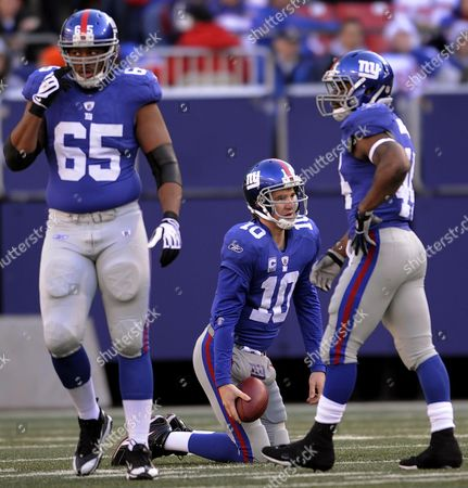 The Giants' Eli Manning (c) Picks Himself Up After Being Sacked As Teammates William Beatty (l) and Ahmad Bradshaw (r) Look on During the First Half of the Game Between the Carolina Panthers and the New York Giants at Giants Stadium in East Rutherford New Jersey on 27 December 2009 United States East Rutherford