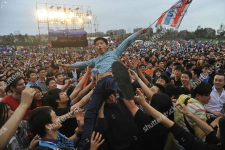 A Person Crowd Surfs As Many Chinese Young People Enjoy the Music at 2011 Chengdu Zebra Music Festival in Rural Chengdu City Southwestern China's Sichuan Province 01 May 2011 This Music Festival is Held From 30 April to 02 May in Poly 198 Park of Chengdu Gathering Chinese Performers Such As Edison Chen Xu Wei Chen Chusheng Yida Huang and Wang Xiaokun to the Chengdu This Music Festival Also Includes Local Drinks Foods Snacks Many Games and Extreme Sports Like Skateboarding Rock Climbing and Bmx Which Attracts As Many As 100 000 Young People China Chengdu