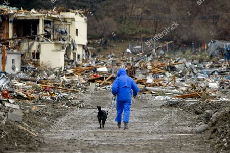 Fifty Nine-year-old Makoto Nakamura and His Dog Walk Together to Look For His Missing Wife Isako in Midst of Debris in Coastal City of Rikuzentakata Iwate Prefecture Northern Japan 16 March 2011 Five Days After a 9 0-magnitude Earthquake Hit Japan Japan Rikuzentakata