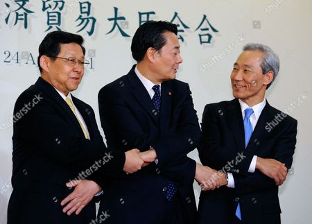 Japanese Economy Trade and Industry Minister Banri Kaieda (c) Joins Hands with His South Korean Counterpart Kim Jong Hoon (r) and Chinese Commerce Minister Chen Deming (l) Prior to Their Trilateral Talks For the 8th Economic and Trade Ministers?? Meeting Between Japan China and South Korea in Tokyo Japan 24 April 2011 the Trade Ministers Are Meeting For Discussions on Issues Including the Impact of Japan's 11 March Earthquake and Tsunami Japan Tokyo