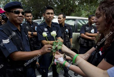 Iranians Hand Roses to the Police After a Protest Outside the United Nations Office in Kuala Lumpur Malaysia 2 March 2011 About 50 Iranians Gathered Outside the United Nations Office to Condemn the Arrest of Opposition Leaders Mirhossein Mousavi and Mehdi Karroubi by Iranian Authorities Malaysia Kuala Lumpur