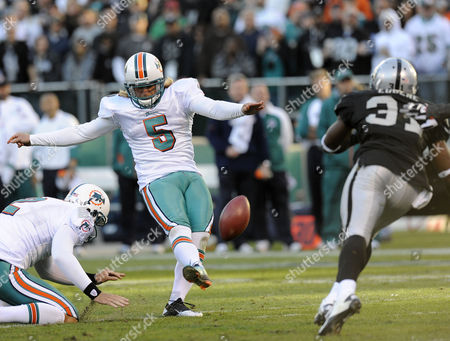 Miami Dolphins Kicker Dan Carpenter (c) Kicks a Field Goal As Oakland Raiders Safety Hiram Eugene Defends During the Second Half at the Oakland-alameda County Coliseum in Oakland California Usa 28 November 2010 the Dolphins Defeated the Raiders 33-17 United States Oakland