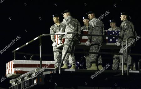 Members of the Us Army Dignified Transfer Team Perform the Dignified Transfer of the Remains of Us Army Sergeant Paul Brooks of Joplin Missouri at the Dover Air Force Base Dover Delaware Usa on 24 May 2009 the Transfer Case Containing Us Army Sgt 1st Class Brian Naseman of Bremen Ohio Rests at Left United States Dover Air Force Base