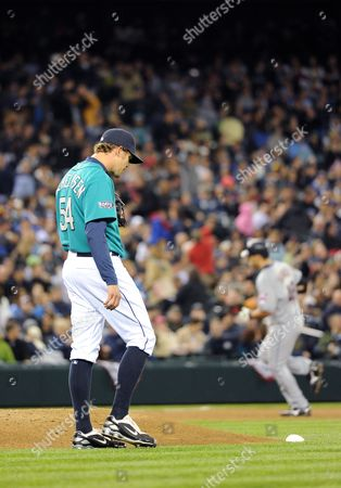 Seattle Mariner Pitcher Tom Wilhelmsen (l) Hangs His Head After Giving Up a Three-run Homer to Cleveland Indian Travis Hafner (r) During Fourth Inning of His Game Against the Seattle Mariners in Seattle Washington Usa on 08 April 2011 United States Seattle