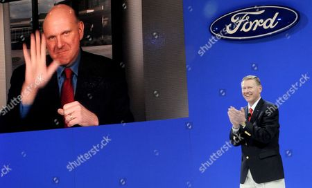 Ford Motor Company President and Ceo Alan Mulally (r) Claps As Steven Ballmer (l) Ceo of Microsoft Corporation on a Video Screen Waves As the Two Companies Announce a New Partnership During a Press Conference at the New York International Auto Show at Jacob Javits Center in New York Usa 31 March 2010 United States New York
