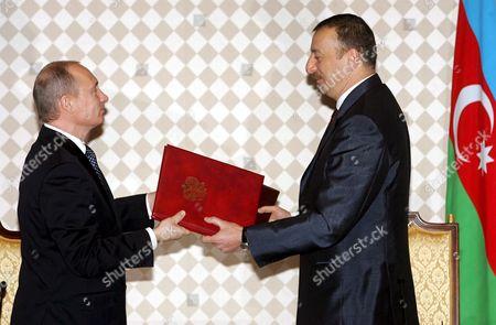 Russian President Vladimir Putin (l) and Azerbaijan President Ilkham Aliev Exchange Documents During Their Meeting in the Azerbaijani Capital Baku Wednesday 22 February 2006