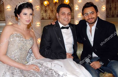 A Picture Made Available on 13 January 2010 Shows Egyptian Singer Tamer Hosny (r) Egyptian Scriptwriter Ahmed Abd El Fatah (c) and His Bride Miss Egypt Fawzaya Mohamed (l) Posing For Photographers During Their Wedding Party Held at El Massa Hotel in Cairo Egypt on 12 January 2010 Egypt Cairo