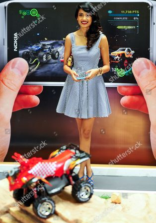 Bollywood Actress Sarah Jane Dias Controls Mini Model Cars Through an Application by Using a Nokia N8 During a Promotional Event For Nokia in Southern Indian City of Bangalore 08 July 2011 India Bangalore