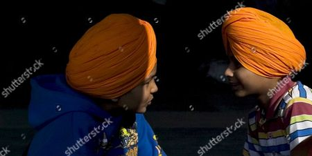 Stock Image of Sikh Children Wearing Turbans in Saffron Colour Which Has a Religious Importance in Sikhism Talk to Each Other Before a Special Pilgrimage Train For Pakistan Arrives at the Railway Station in the Northern Indian City of Amritsar 11 November 2008 Thousands of Pilgrims From All Over the World Are Expected to Visit Pakistan's Various Sikh Shrines to Take Part in the Birth Anniversary Celebrations of the First Sikh Guru Or Master Sri Guru Nanak Dev Ji Which Will Be Observed On 13 November 2008