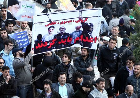 Iranian Demonstrators Hold a Poster of Opposition Leaders Mir-hossein Mousavi Mehdi Karoubi and Mohamad Reza Khatami with Text Reading in Persian They Should Be Hanged As Thousands of Iranian Government Supporters Stage a Protest Demonstration Against Opposition Leaders on 18 February 2011 in Tehran Iran More Than 200 Legislators Several Clerical Groups and Government Supporters Have Called For the Arrest and Execution of Mir-hossein Moussavi and Mehdi Karroubi For Allegedly Undermining the Islamic System and Collaborating with Foreigners Thousands of Government Supporters Gathered After Friday Prayers in Enqelab Square in Central Tehran and Took Up the Call Shouting 'Moussavi and Karroubi Should Be Hanged ' Iran (islamic Republic Of) Tehran