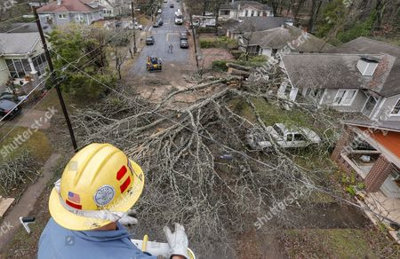 Lineman David West with East Point Power surveys the damage while helping restore power after a large tree fell and hit a home and several cars as thunderstorms moved through East Point, Georgia, USA, 03 January 2017. Heavy storms in the southern United States left at least five people dead according to reports, including four in one mobile home in Rehobeth, Alabama.