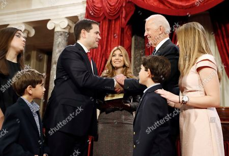 Stock Picture of Joe Biden, Marco Rubio, Jeanette Rubio Vice President Joe Biden, right, shakes hands with Sen. Marco Rubio, R-Fla., with his wife Jeanette Rubio holding a Bible, and other family nearby, after administering the Senate oath of office during a mock swearing in ceremony in the Old Senate Chamber on Capitol Hill in Washington, as the 115th Congress begins