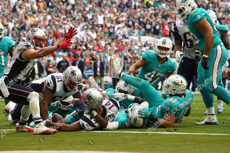 Michael Floyd #14 of New England is tackled by Bobby McCain #28, Tony Lippett #36, and Spencer Paysinger #42 of Miami after scoring a touchdown during the NFL football game between the Miami Dolphins and New England Patriots at Hard Rock Stadium in Miami Gardens FL. The Patriots defeated the Dolphins 35-14