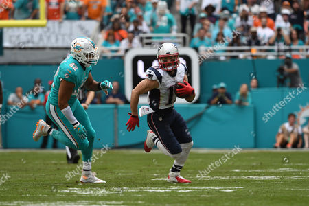 Julian Edelman #11 of New England runs past Spencer Paysinger #42 of Miami during the NFL football game between the Miami Dolphins and New England Patriots at Hard Rock Stadium in Miami Gardens FL. The Patriots defeated the Dolphins 35-14