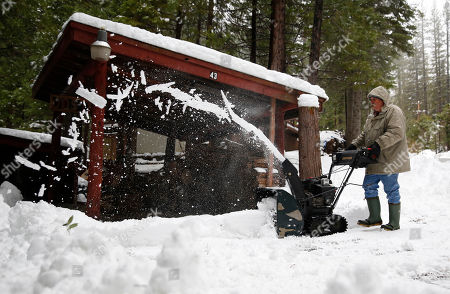 Joe Johnson clears the snow from a neighbor's driveway near Kyburz, Calif., . The California Department of Water Resources held the first manual snow survey of the season near Phillips Station near Echo Summit, onTuesday. The survey showed the snowpack at 53 percent of normal at the site for this time of year