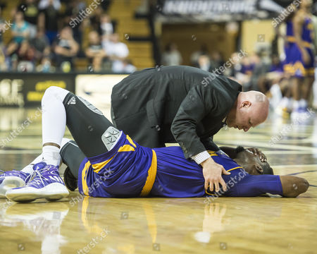 Orlando, FL, U.S: East Carolina guard Caleb White (2) is tended to by athletic trainer Nate Clark after a collision with a Central Florida player during NCAA basketball game. Central Florida defeated East Carolina 48-45 at CFE Arena in Orlando, Fl