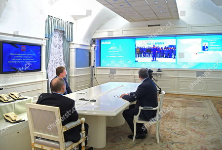 Stock Picture of Russian President Vladimir Putin (C), Crimean head Sergey Aksyonov (R) and Acting Governor of Sevastopol Dmitry Ovsyannikov (L) watch a ceremony to launch natural gas supplies to Crimea from mainland Russia via a new gas pipeline connecting the Krasnodar Territory with the Crimea peninsula during a live video link in Moscow
