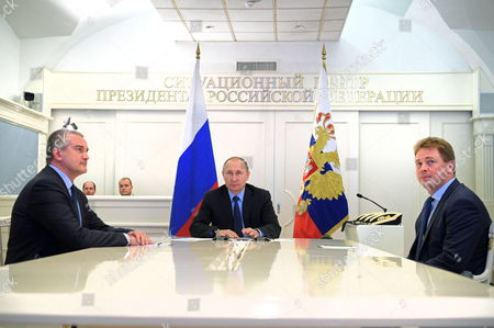 Russian President Vladimir Putin (C), Crimean head Sergey Aksyonov (L) and Acting Governor of Sevastopol Dmitry Ovsyannikov (R) watch a ceremony to launch natural gas supplies to Crimea from mainland Russia via a new gas pipeline connecting the Krasnodar Territory with the Crimea peninsula during a live video link in Moscow