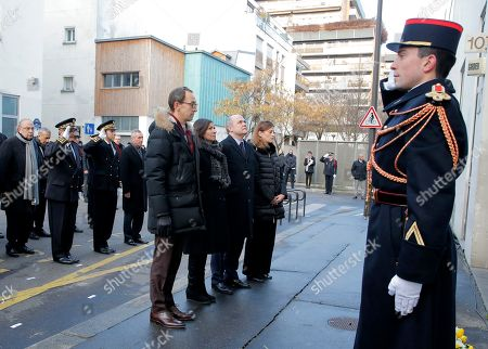District mayor Francois Vauglin, Paris mayor Anne Hidalgo, French Interior Minister Bruno Leroux and State Secretary in charge of Victims Juliette Meadel stand at attention at the place of the attacks of Charlie Hebdo to mark the second anniversary of the attack, Thursday, Jan.5, 2017