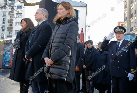 From left, Paris mayor Anne Hidalgo, French Interior Minister Bruno Leroux and State Secretary in charge of Victims Juliette Meadel stand attention at the place of the attack where policeman Ahmed Merabet was killed to mark the second anniversary of the attack